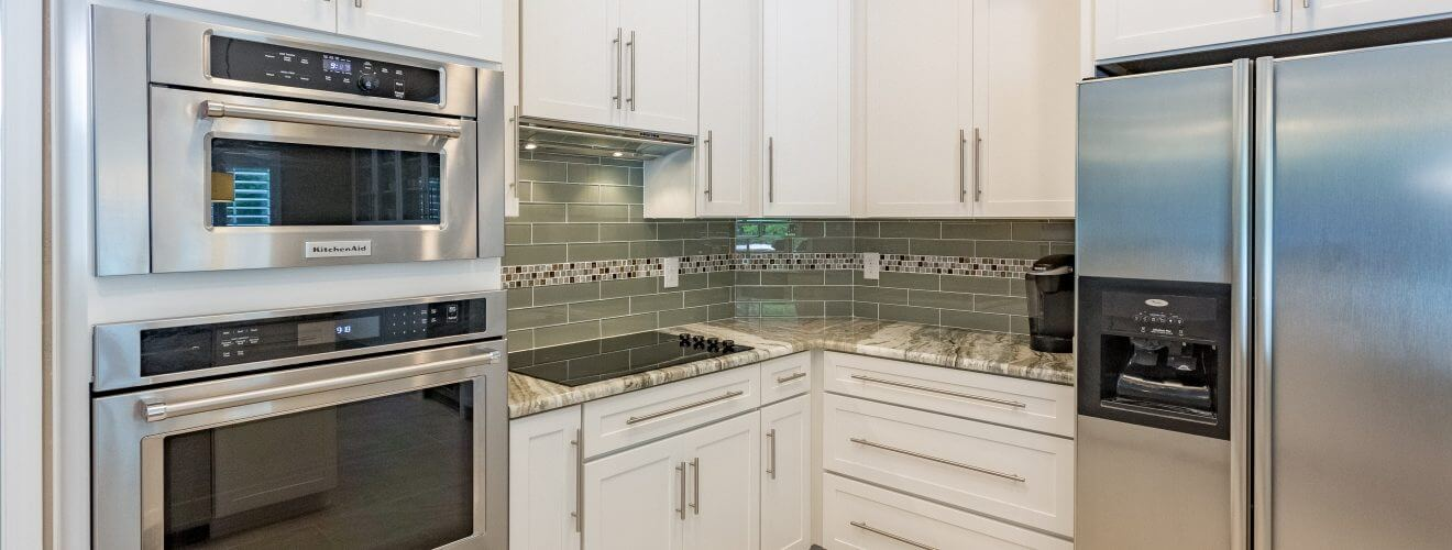 White Shaker cabinets with crown molding, glass tile backsplash and stainless steel appliances and hardware.