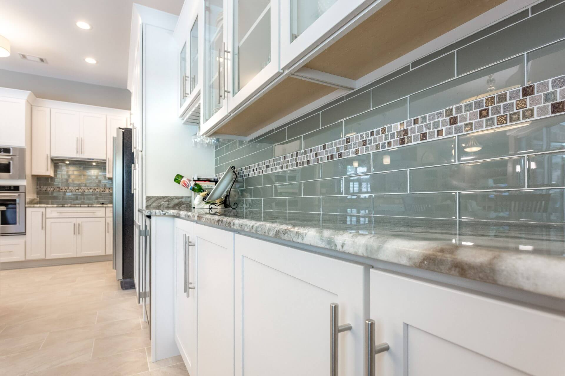 White shaker cabinets featuring a glass subway tile backsplash with tile insert, granite countertops and modern stainless steel pulls