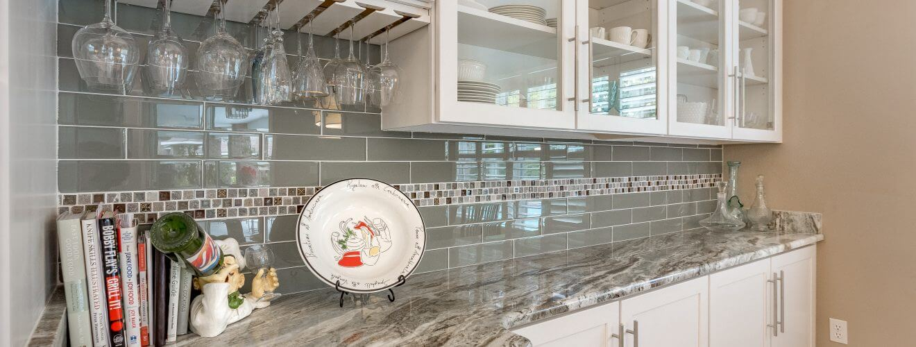 Custom Shaker cabinets with glass panels, granite countertops, and glass tile backsplash