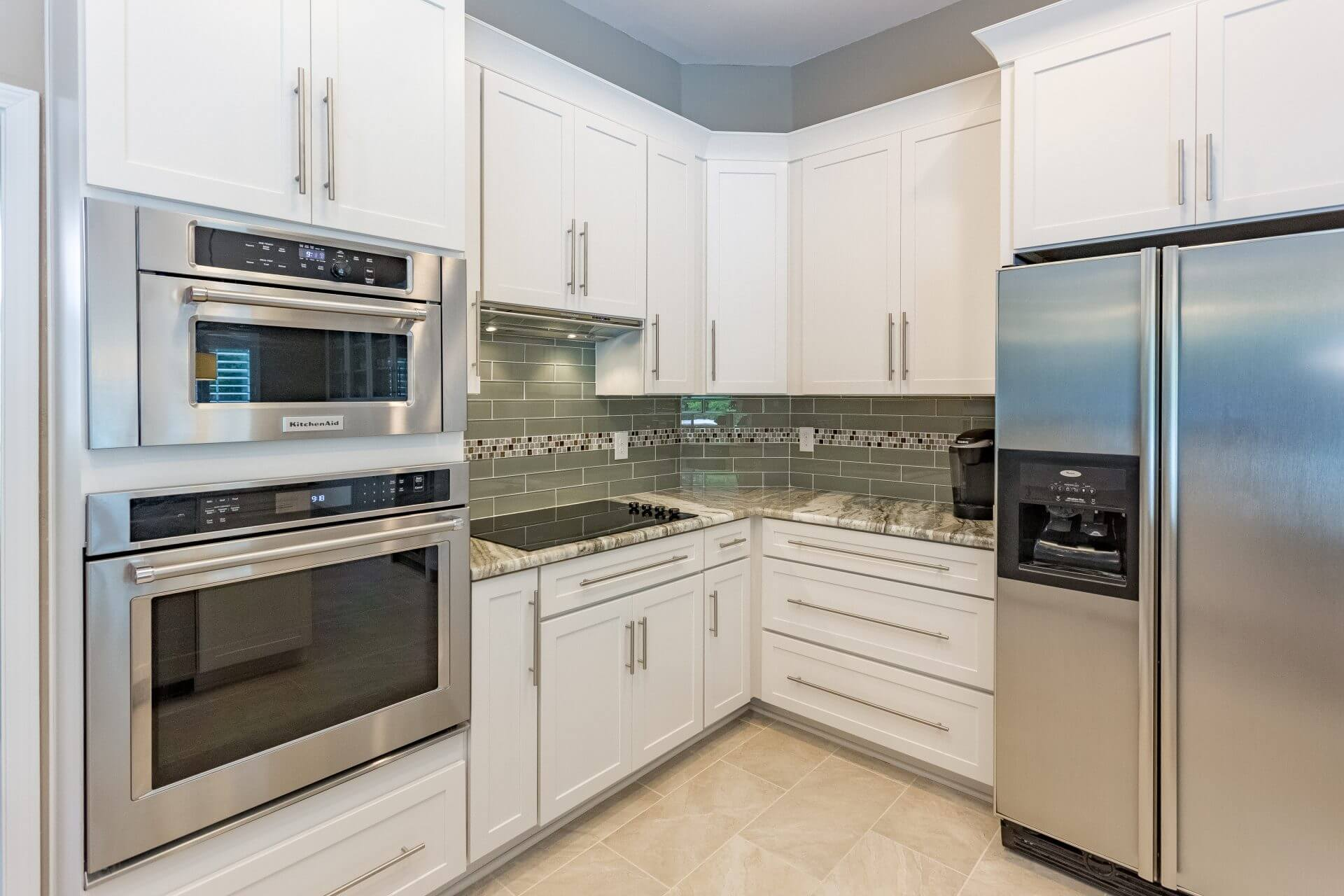 Services include installation of White Shaker cabinets with crown molding, glass tile backsplash and stainless steel appliances and hardware.