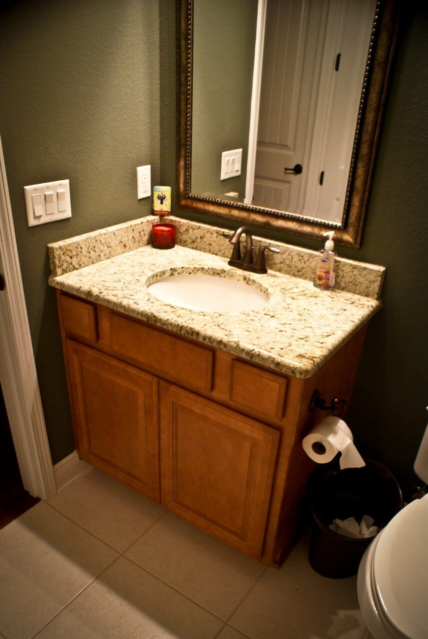 Custom bathroom cabinetry with granite countertop and backsplash