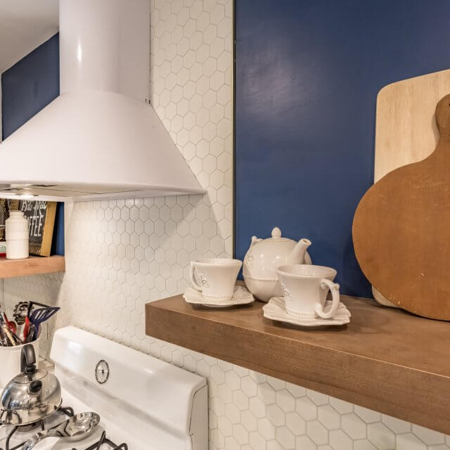 After: Mid-century modern kitchen remodel features a clean, white oval backsplash