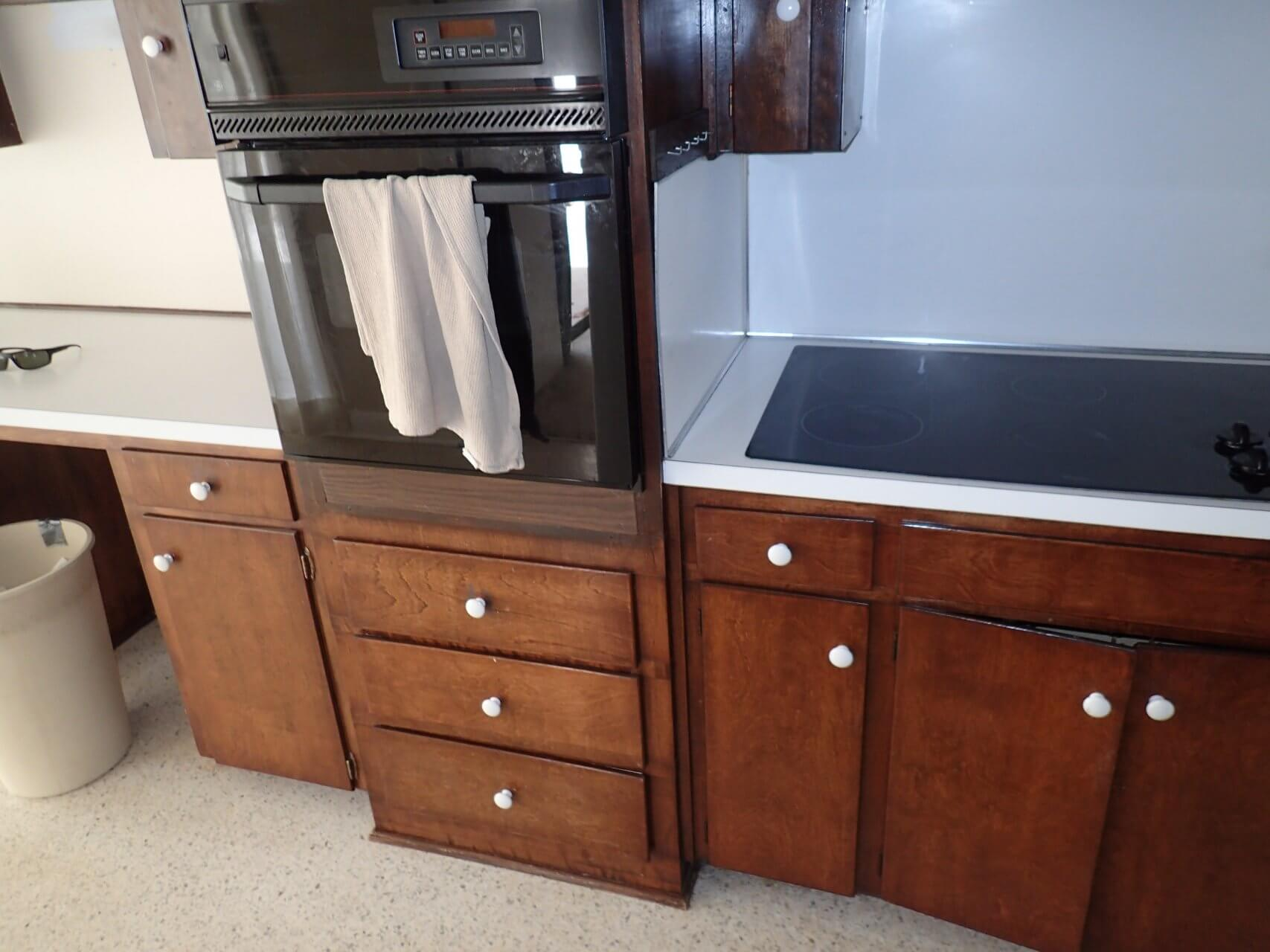 Before: Outdated dark brown kitchen cabinets with oven and microwave in kitchen remodel