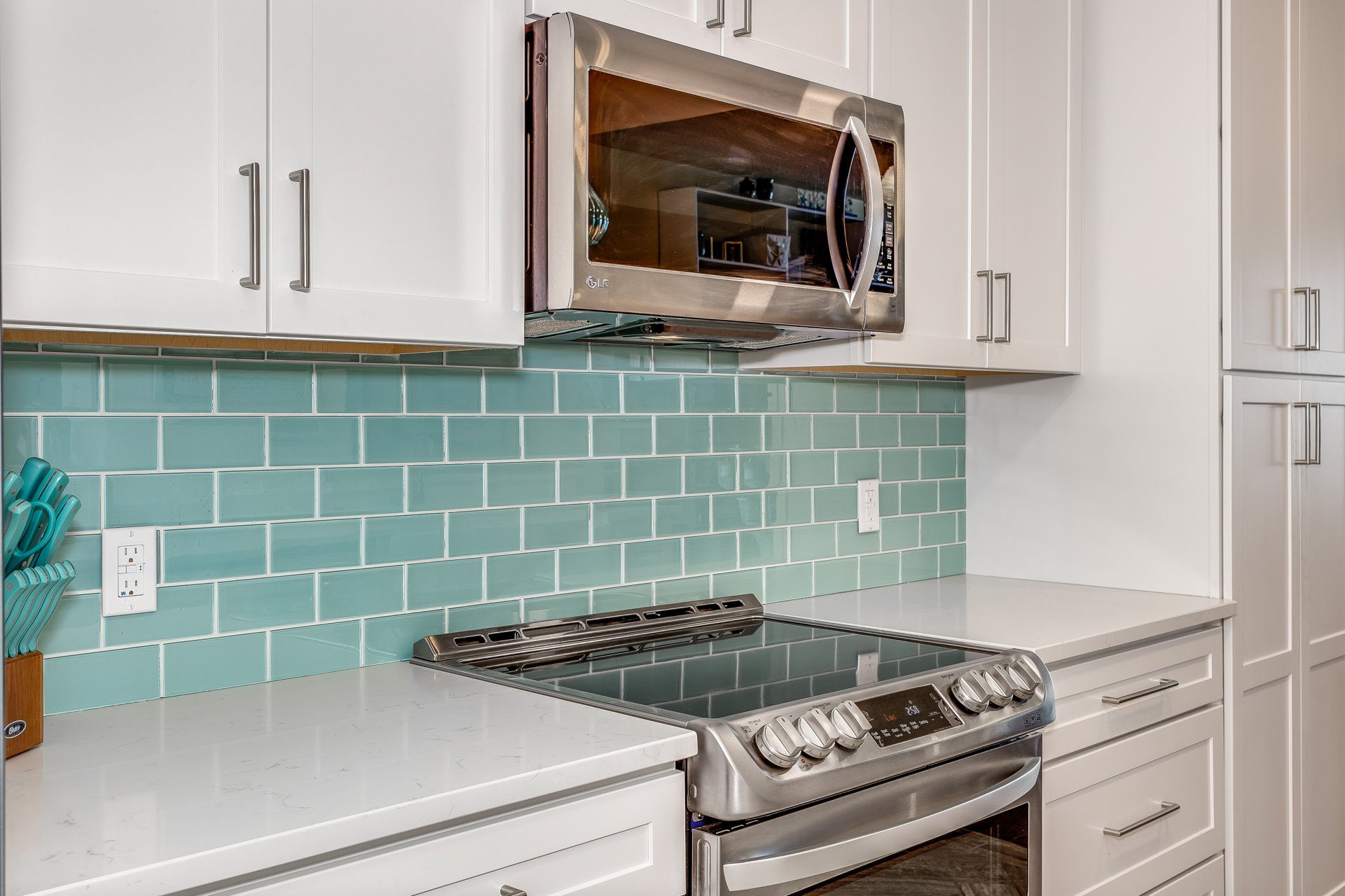 Detail of glass subway tile backsplash in soft mint